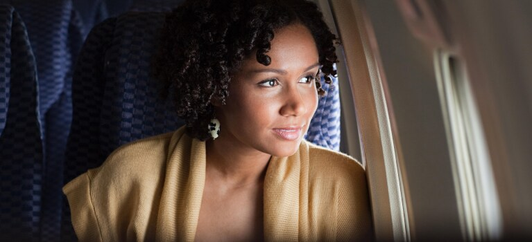 woman smiling out airplane window
