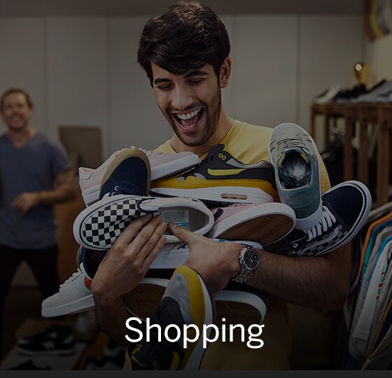 Male laughing with overflowing arms full of sneakers. Text over image - Shopping.