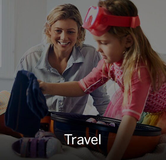 Child packing little suitcase with clothes. Mother in background smiling. Text over image - Travel.
