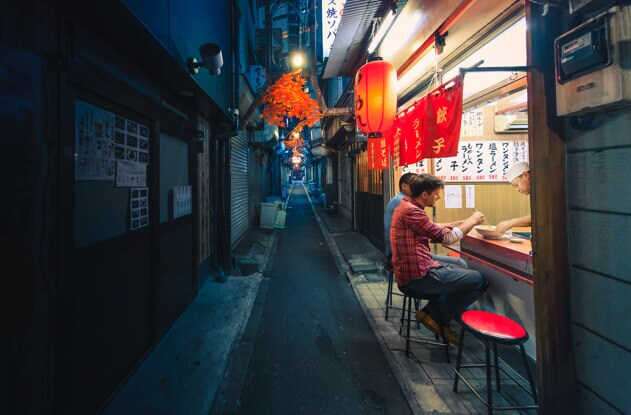 Two friends dine at a soup street vendor at night