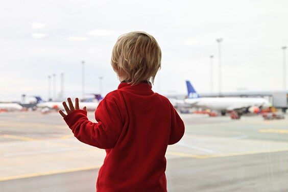 Child looking out airport window.