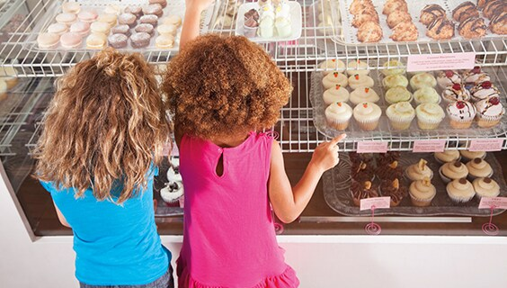 Two children looking at baked goods display - American Express