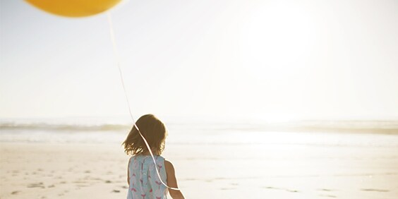 Child on beach with balloon - American Express