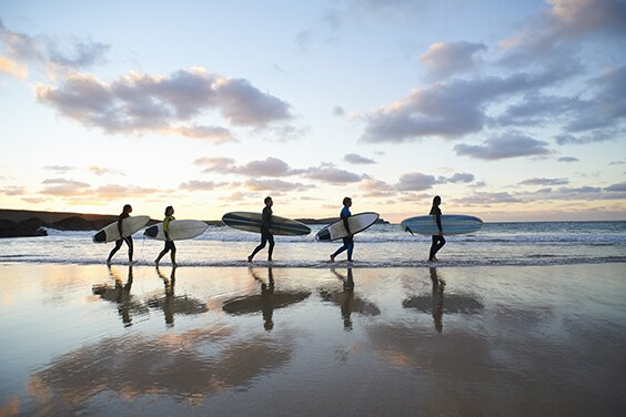 Five people walking on the beach carrying surfboards - American Express