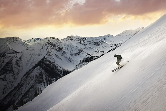 Skier gliding down steep slope - American Express