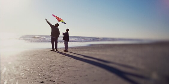 Father and son flying a kite on the beach - American Express