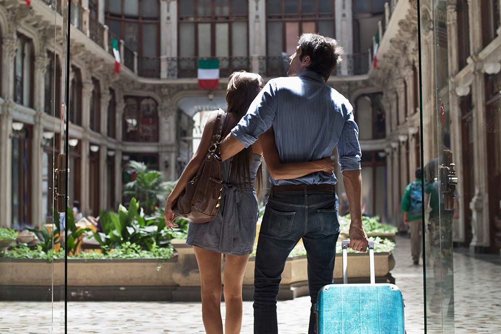 Couple with arms around each other pulling suitcase