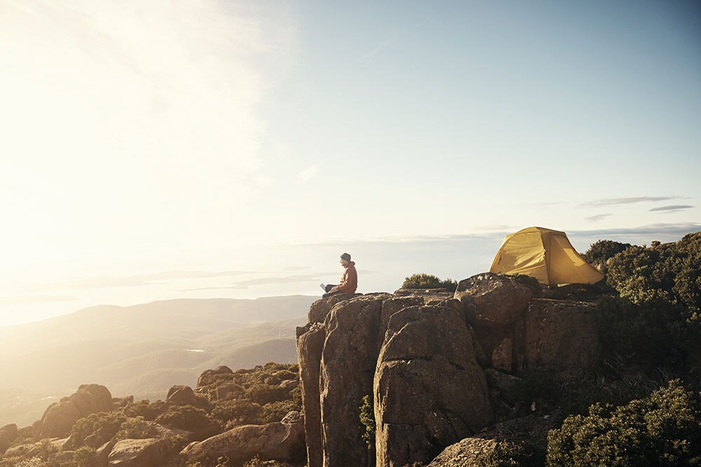 Man camping near cliff edge