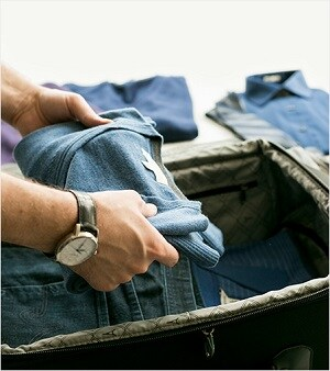 Man packing jeans into suitcase