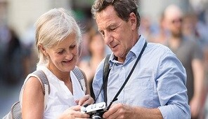 Travelling couple viewing photos on camera