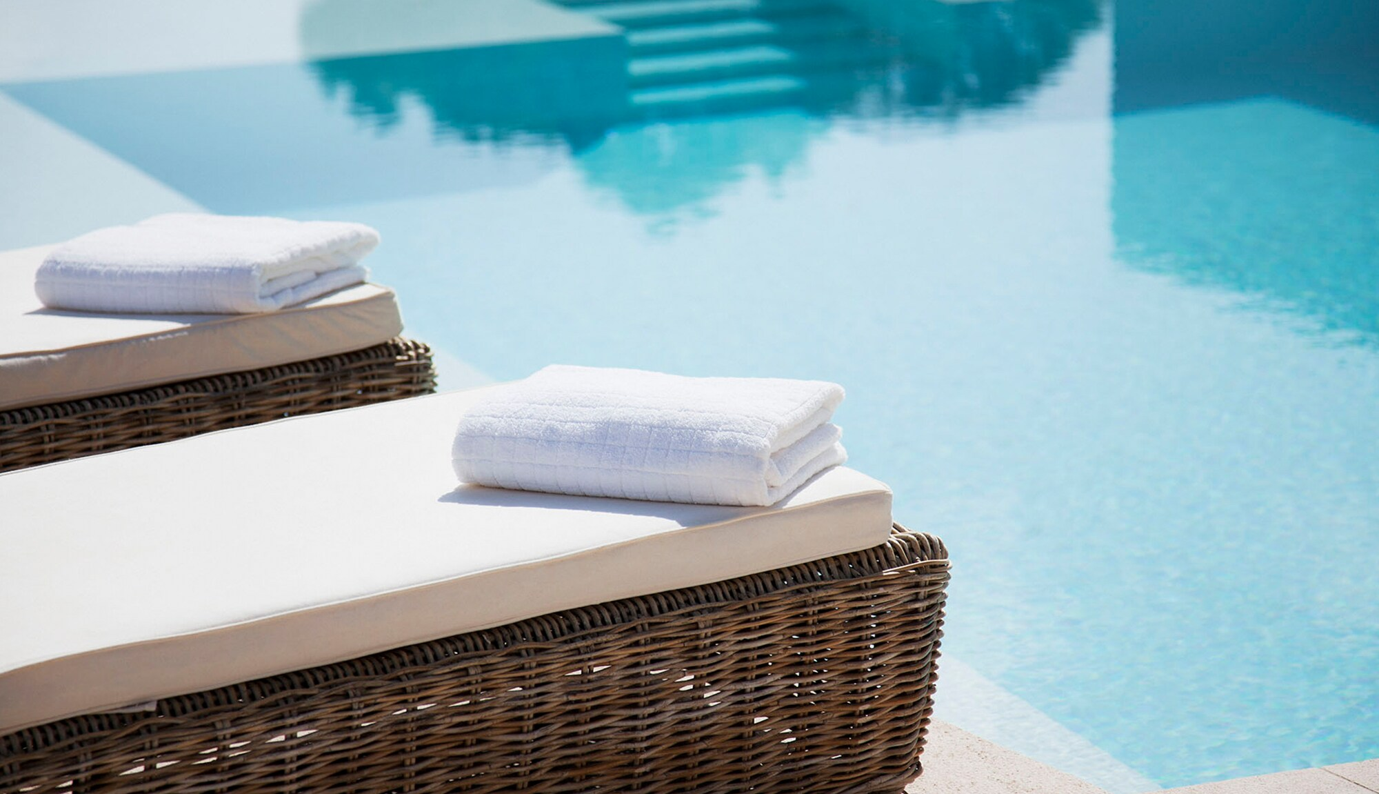 Transfer Points to Airline Partners – towels by a resort pool.