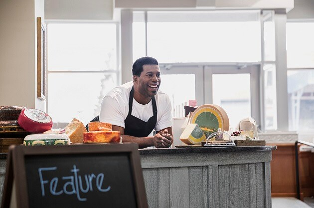 An image of a man in a café smiling