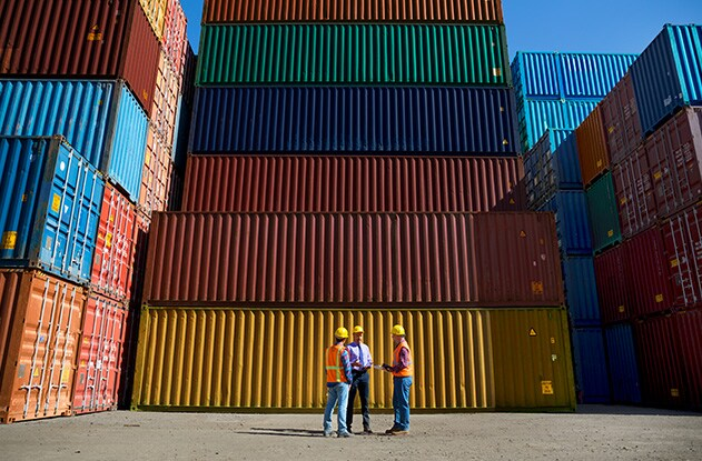 An image of men in high vis vests in front of a stack of sea containers