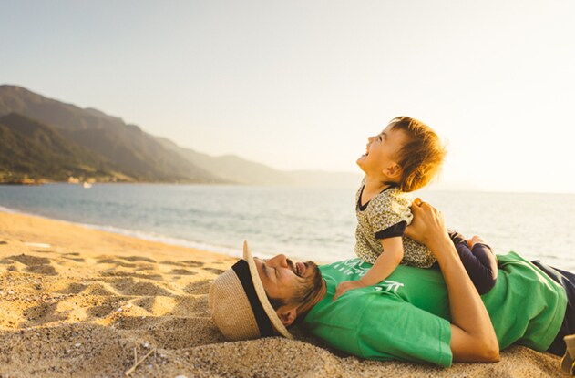 Image of a father and son laughing on the beach