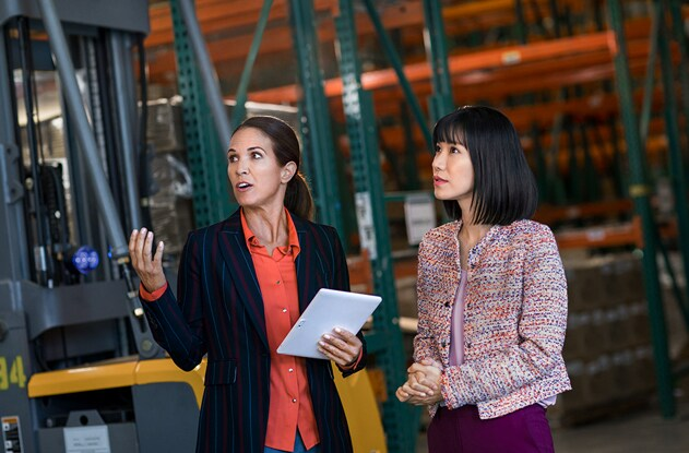 Two woman discussing business while observing an event in a factory.