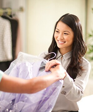 woman holding dry cleaning
