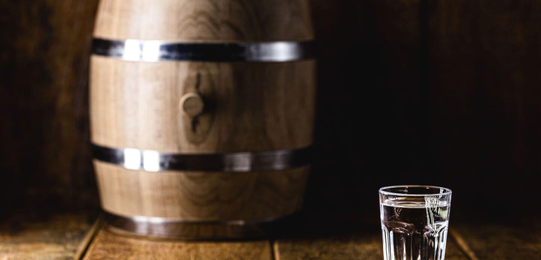 Ein Glas mit klarem Inhalt vor einem Holzfass