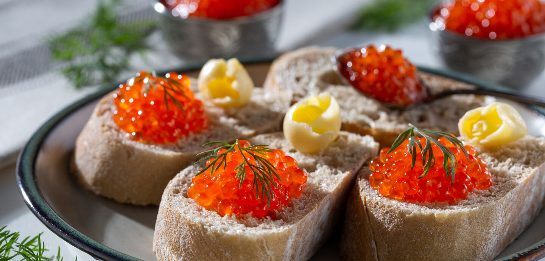 Rote Fischeier und daneben Butterstückchen auf Baguettescheiben