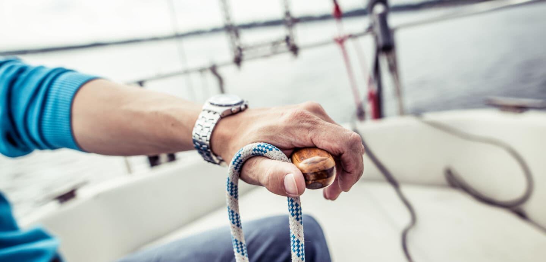 Die linke Hand eines Mannes hält das Steuer eines Segelboots