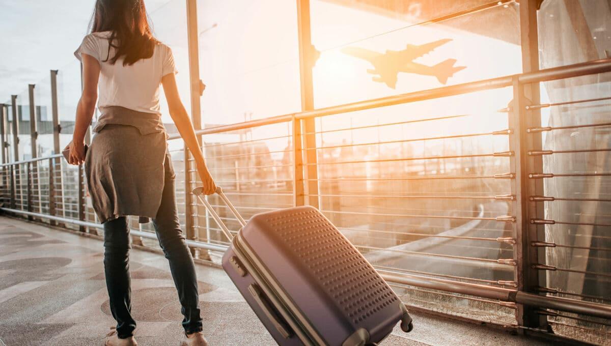Frau zieht Koffer durch den Flughafen