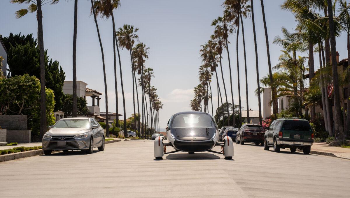 Ein futuristisches Fahrzeug fährt in der Sonne auf palmengesäumter Straße