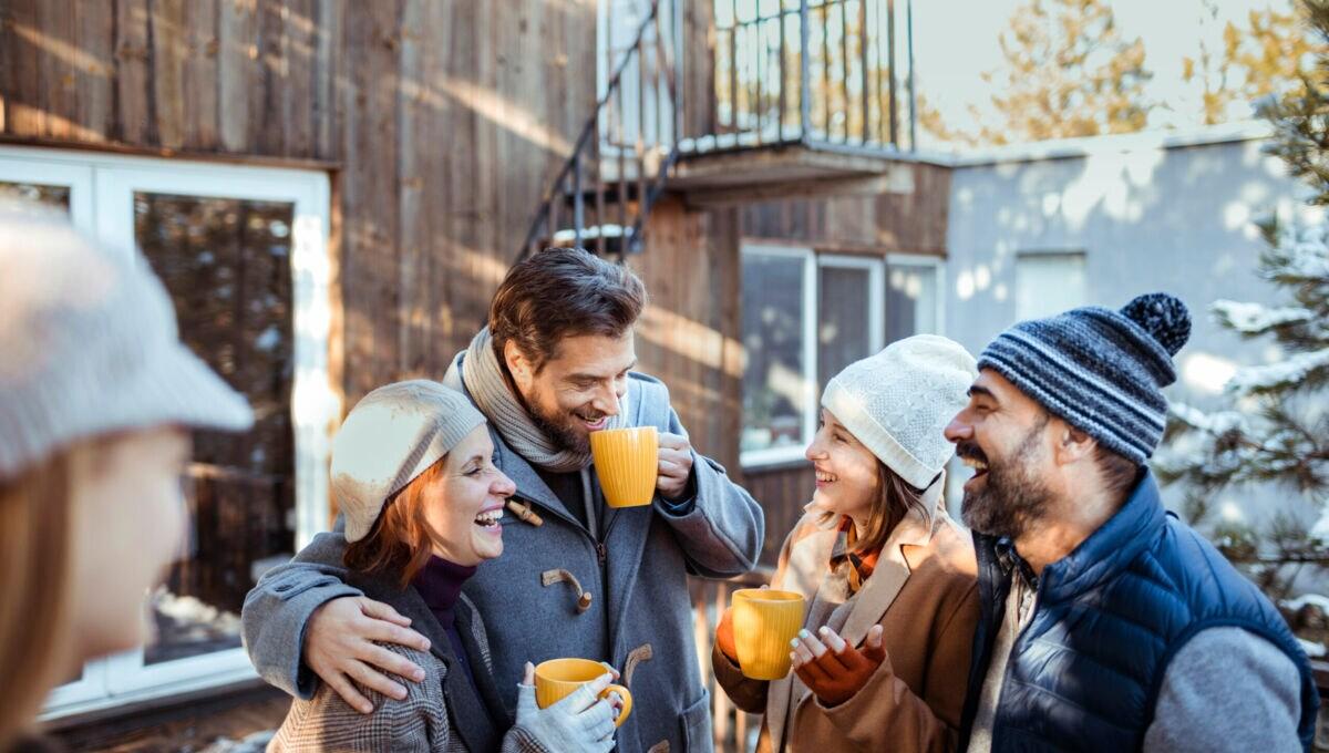 Freunde stehen im Winter vor eine Holzhütte und lachen und reden miteinander