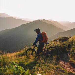 Mountainbiker steht mit seinem Rad auf einem Berg und schaut ins Tal