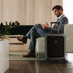 Ein Mann in einem Sessel, neben ihm steht ein Koffer