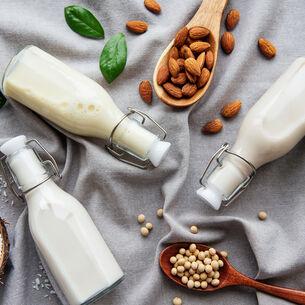 Auf einem grauen Tuch liegen drei Bügelflaschen mit weißlicher Flüssigkeit, Kokosraspel, Kichererbsen und Mandeln