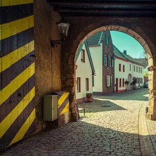 Ein historisches Stadttor mit gelb-schwarz gestreifter Tür
