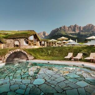 Hotelanlage mit begrüntem Dach und Liegen am Außenpool vor Bergpanorama