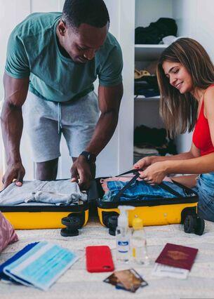Ein Mann und eine Frau packen einen Koffer für eine Urlaubsreise.