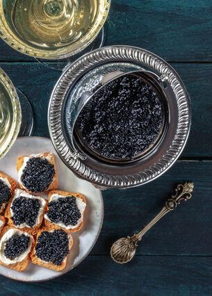 Sicht von oben auf eine Schüssel mit Kaviar und einen Teller mit Zwieback Creme und Kaviar