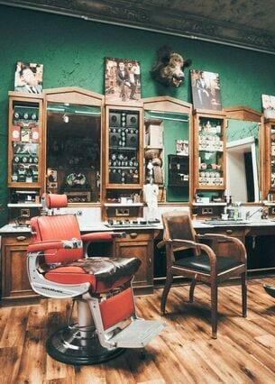 Das Interieur eines Vintage-Barbershops mit dunkelgrünen Wänden, Ledersofa und Retro-Friseurstühlen