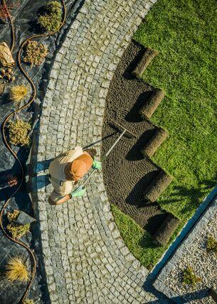 Luftaufnahme einer Person, die auf einem gepflasterten Weg stehend eine Fläche mit Rollrasen in einem Garten bearbeitet