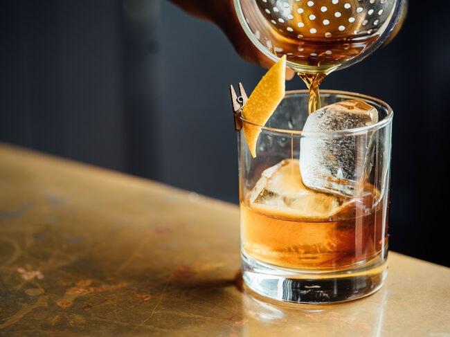 Ein Trinkglas mit Eis und Zitronenschale wird mit Whisky befüllt